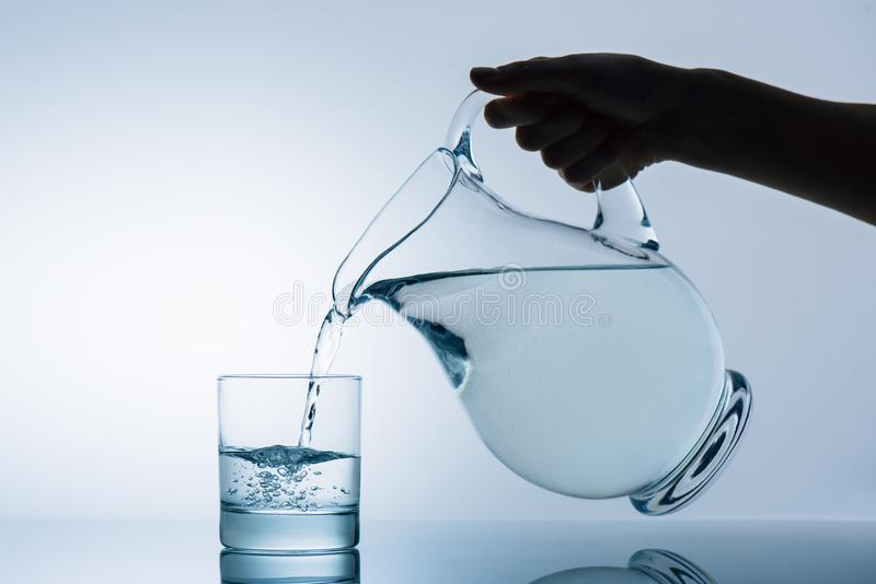 Cropped image of woman pouring water from transparent jug royalty free stock images