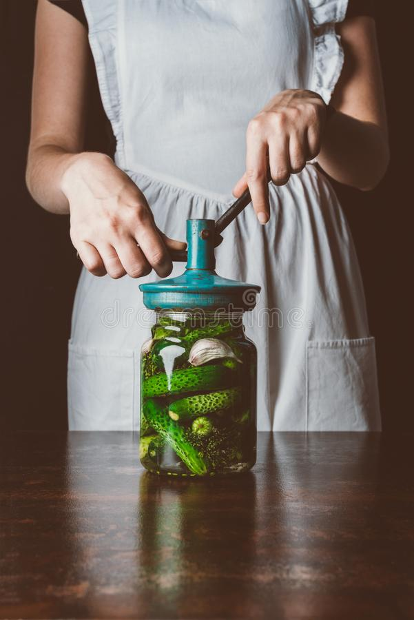cropped image of woman preparing preserved cucumbers in glass jar stock photos