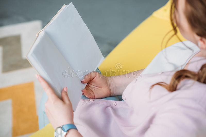 Cropped image of woman reading book on sofa. At home stock photo