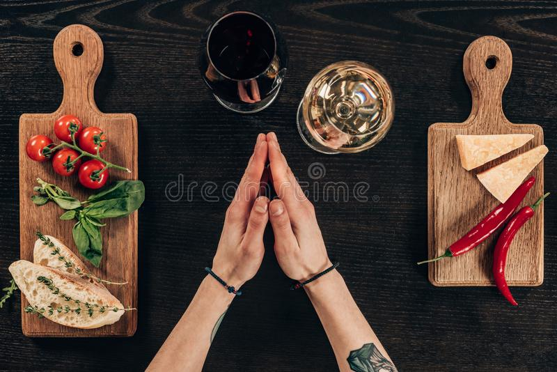 Woman sitting at table with wine and parmesan cheese. Cropped image of woman sitting at table with wine and parmesan cheese stock images