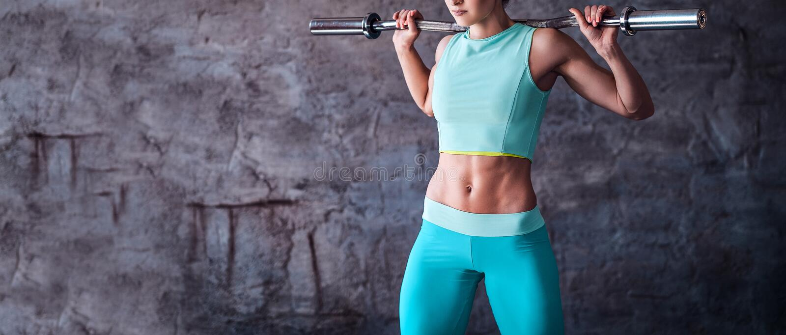 Cropped image of a woman in sportswear workout with a barbell in the gym against a gray wall stock photo