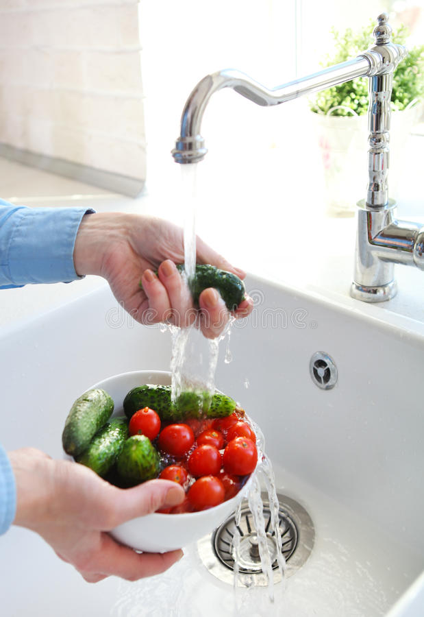 Cropped image of woman washing tomatoes and cucumbers at the kit royalty free stock image