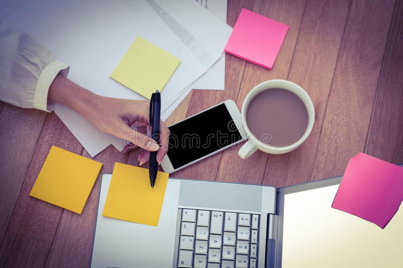 Cropped image of woman writing on sticky notes royalty free stock image