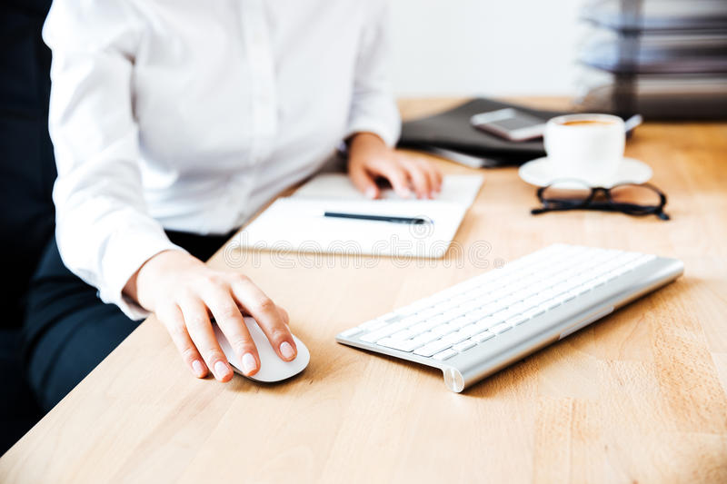 Cropped image of women`s hands using keyboard and mouse. At the office royalty free stock images