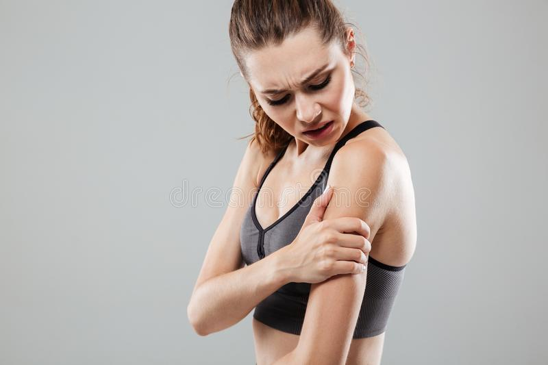 Cropped image of young fitness woman having arm pain. While standing over gray background stock images
