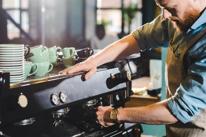Cropped image of young male barista in apron using. Coffee machine royalty free stock photography