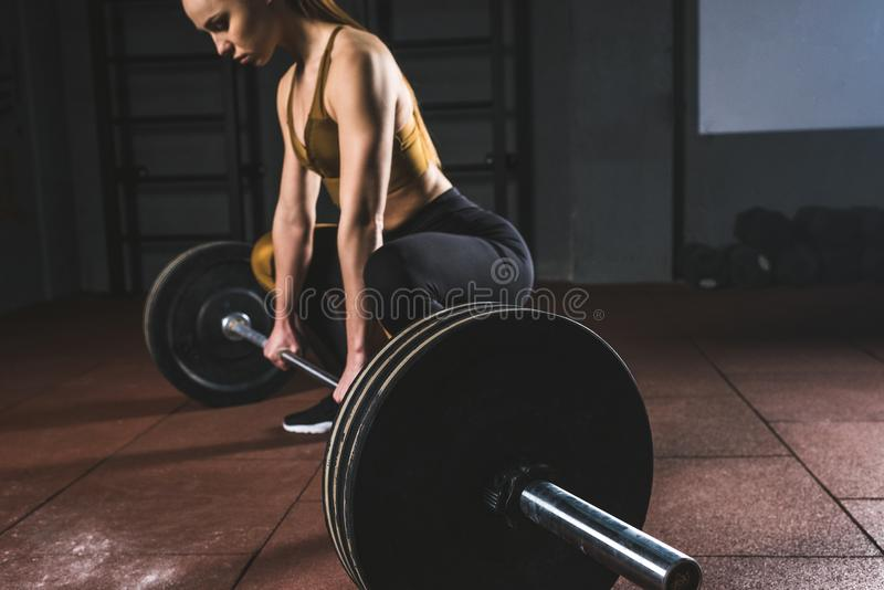 Cropped image of young sportswoman. Prepare to raise barbell in gym stock photos