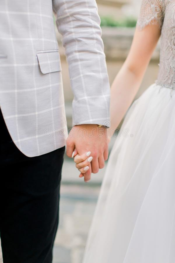 Cropped image of young wedding couple holding hands, wedding ceremony day. Hands of the man and woman in love stock photography