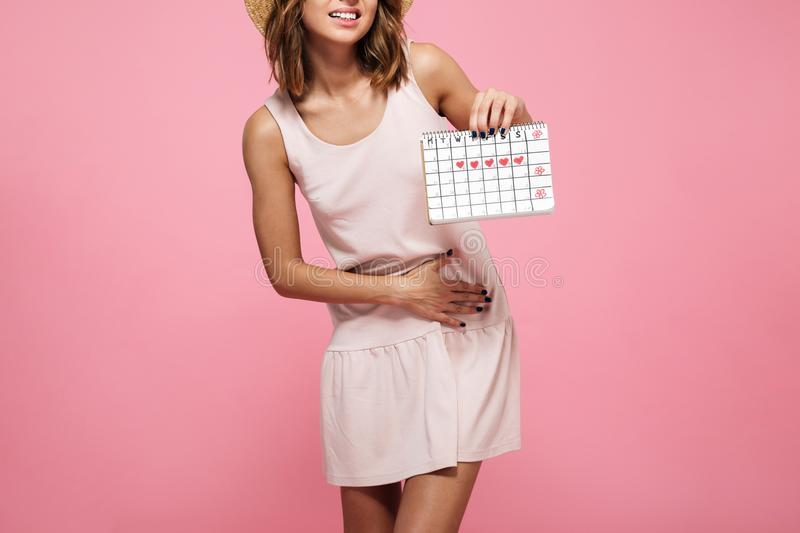 Cropped image of a young woman in dress suffering. From belly pain and showing her periods calendar isolated over pink background stock photos