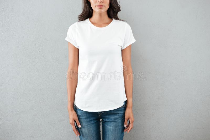 Cropped image of a young woman dressed in t-shirt. Cropped image of a young woman dressed in blank white t-shirt standing still standing isolated over gray stock photos
