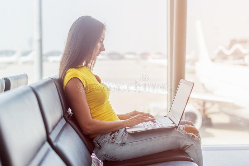 Cropped image of young woman holding a laptop on lap typing keyboard indoors in public place stock images