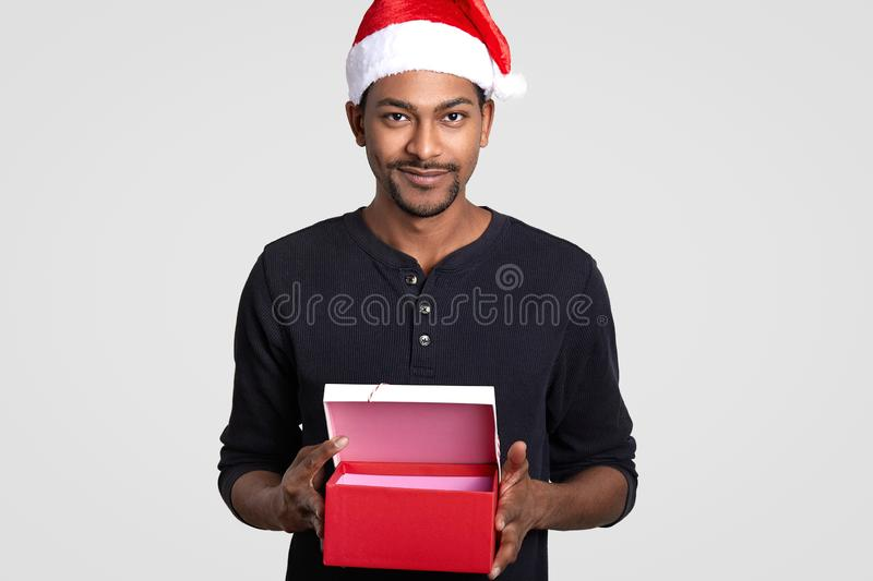 Cropped isolated shot of dark skinned young male wears Santa Claus hat, carries opened red gift box, suggests you to buy present. For Christmas, stands against stock images