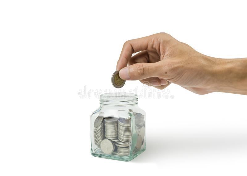 A cropped of man hand holding coin over many coins in glass jar on white background royalty free stock images