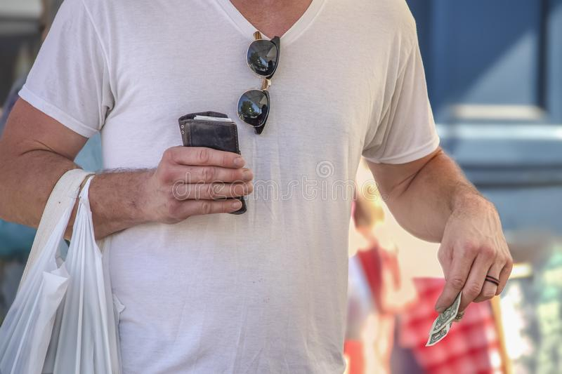 Cropped man in white teeshirt with sunglasses hanging at neck holding plastic bag of what he has purchaed and worn billfold and Am. Erican dollars in the other stock photos