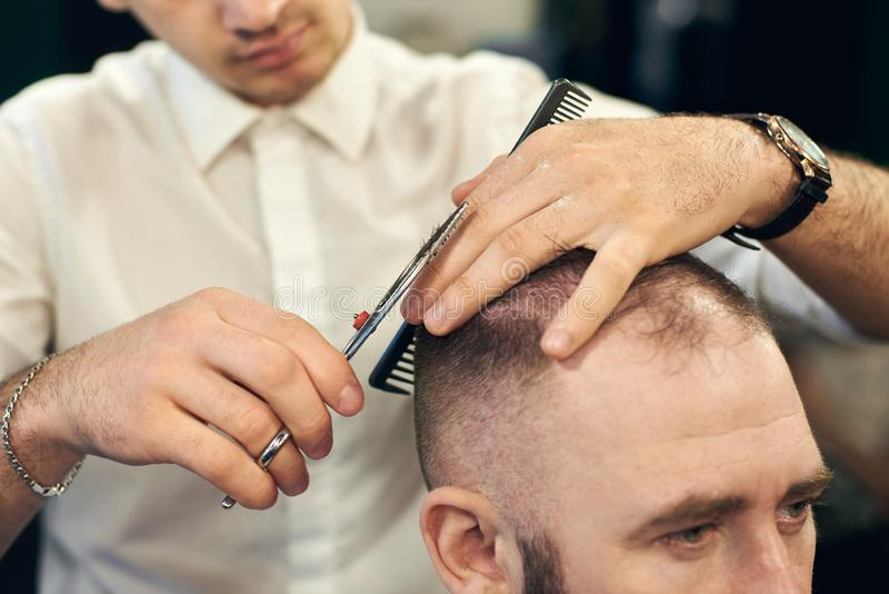 Male hairdresser making short haircut for client in modern barbershop. Concept of traditional haircutting with scissors. stock images