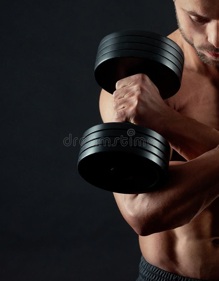 Cropped photo of athletic man keeping dumbbells stock photography
