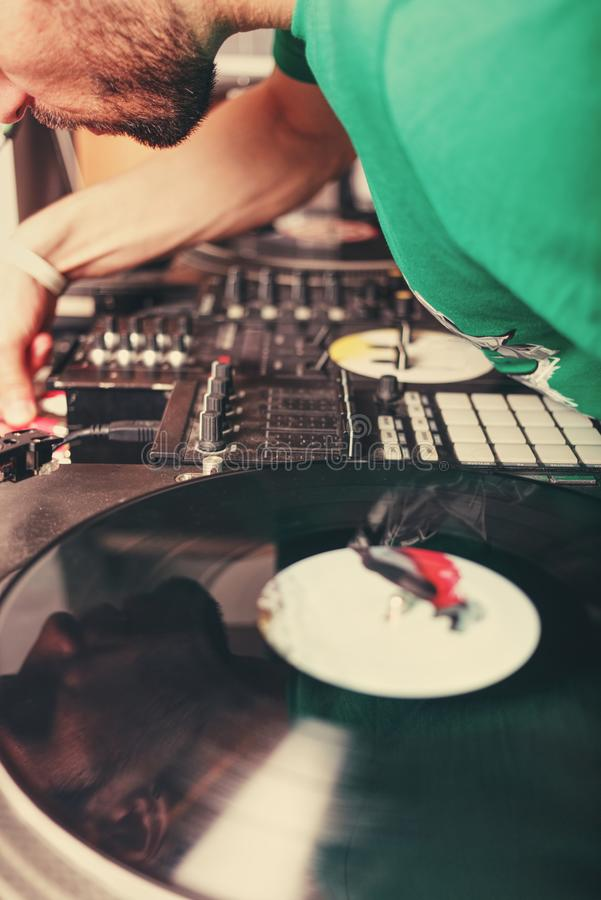 Bearded DJ and vinyl record. Cropped photo of bearded DJ selecting new track on vinyl record royalty free stock image