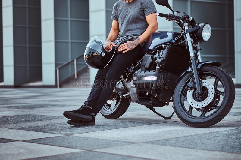 Cropped photo of a brutal bearded male in a gray t-shirt and black pants holds a helmet sitting on his custom-made retro royalty free stock photos
