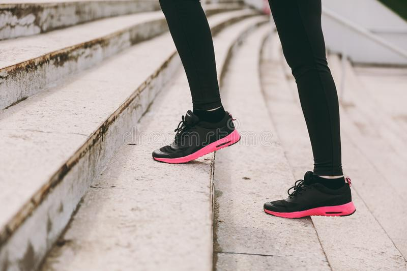 Cropped photo close up of female legs in sportswear, black and pink woman sneakers doing sport exercises, climbing on stock images