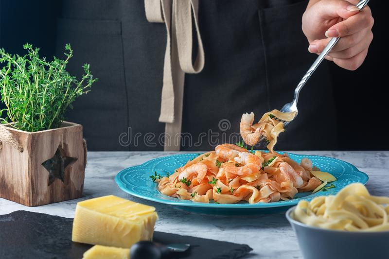 Cropped photo, a girl wrapped a spaghetti on a fork. Mafaldin pasta with tomato sauce, shrimp and thyme stock photos