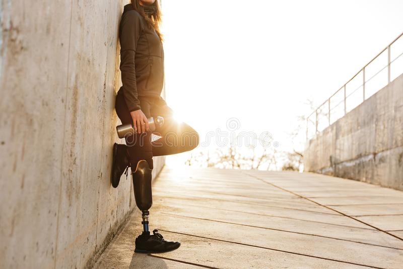 Cropped photo of handicapped woman with prosthesis leg in sports. Wear standing outdoor over concrete wall with sunlight royalty free stock photography