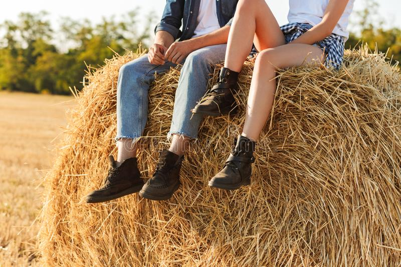 Cropped photo of lovely man and woman sitting on big haystack in. Cropped photo of lovely men and women sitting on big haystack in golden field during sunny day stock image