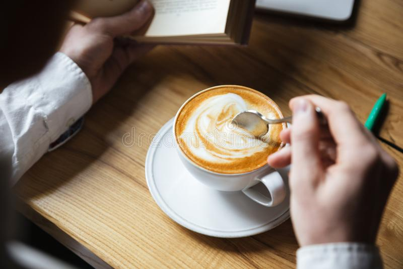 Cropped photo of man in white shirt stirring coffee while reading book royalty free stock photos