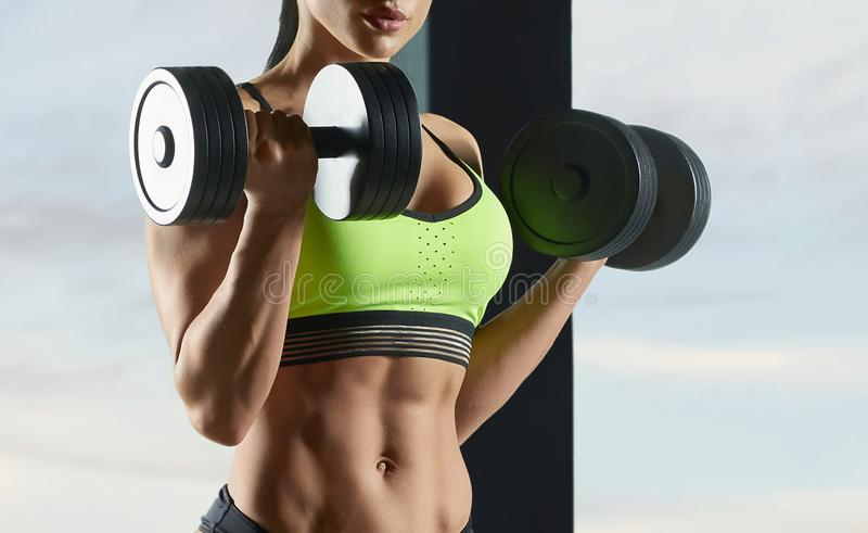Cropped photo of strong fit model lifting in gym heavy dumbbells. stock images