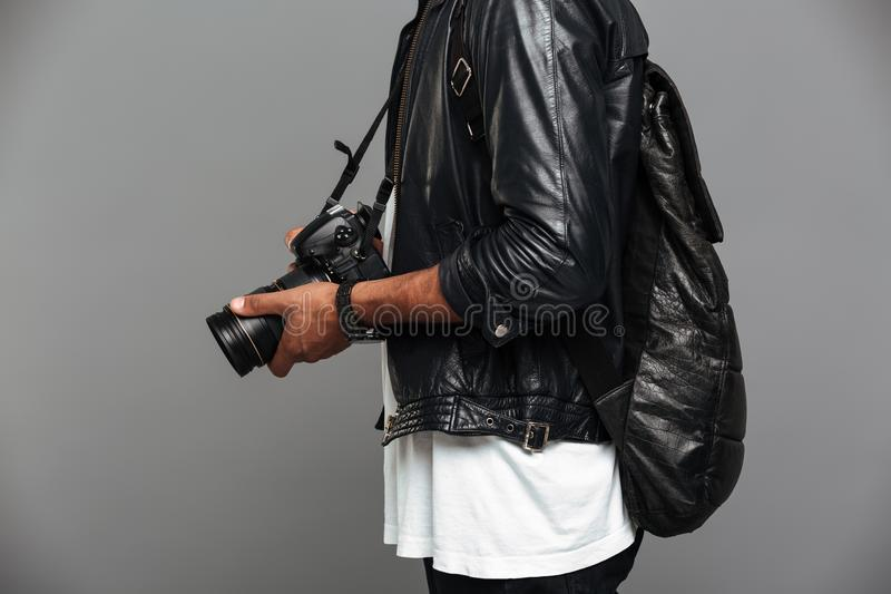 Cropped photo of stylish african man with backpack holding photo. Camera, isolated on gray background stock photos