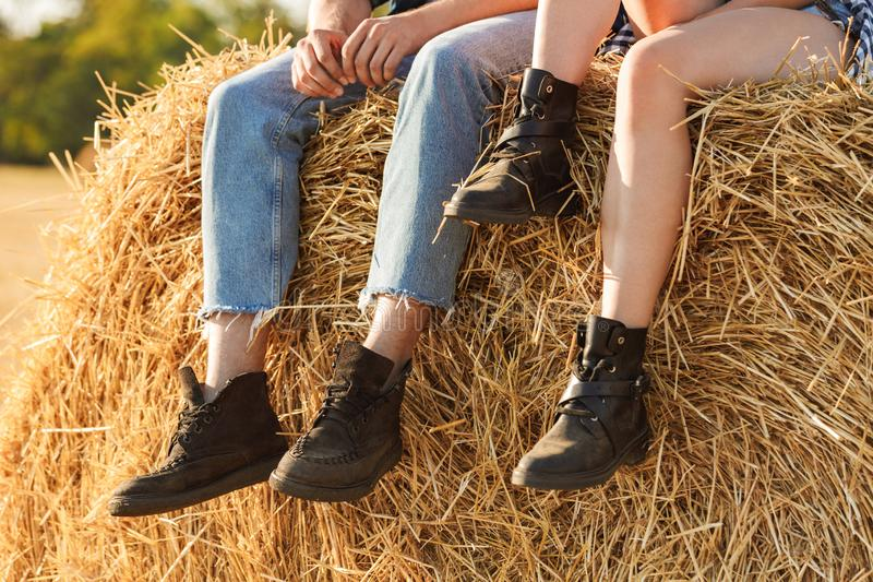 Cropped photo of stylish man and woman sitting on big haystack i. Cropped photo of stylish men and women sitting on big haystack in golden field during sunny day royalty free stock image