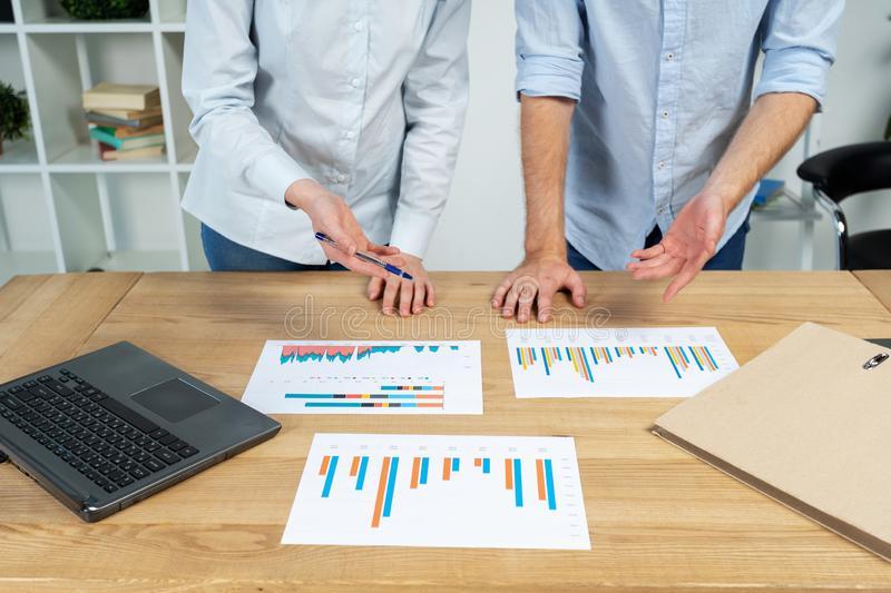 Cropped photo of two person in formalwear shirt stand behind table in bright loft interior workstation point at blanks with graphs.  stock photography