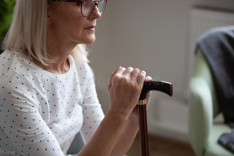 Cropped upset mature woman in glasses holding cane, sitting alone. Cropped photo upset mature woman in glasses holding cane, thinking about future, disabled stock photos