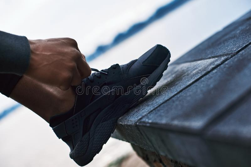 Cropped photo of young handsome african man which strings sneakers stock image