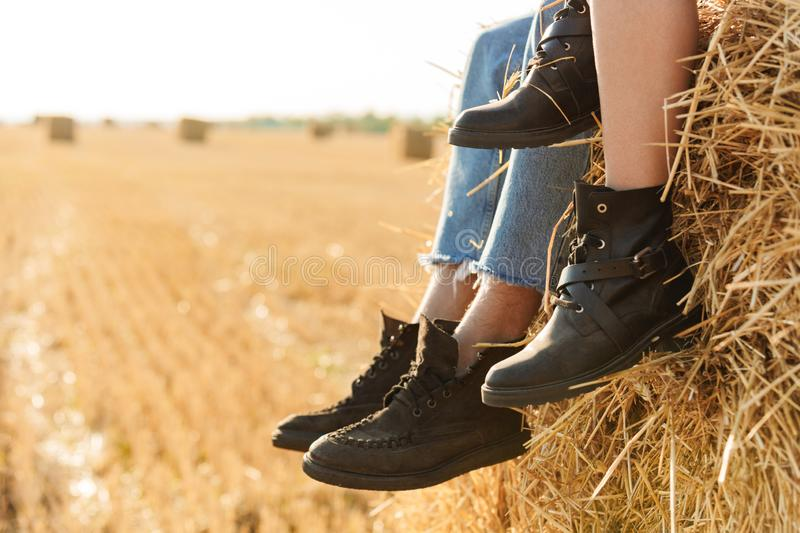 Cropped photo of young man and woman sitting on big haystack in. Cropped photo of young men and women sitting on big haystack in golden field during sunny day stock image