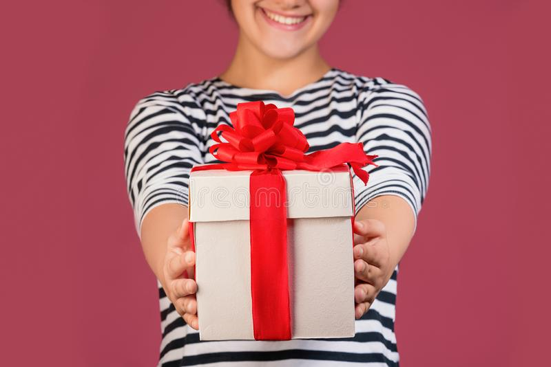 Cropped picture of girl with gift box isolated over pink background stock image