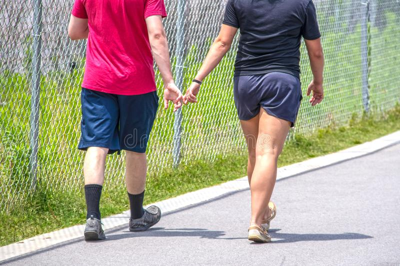 Cropped  picture of two young adults wearing shorts and tee shirts on paved walking trail with fingers intertwined - cropped and stock photos