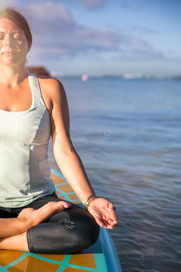 Cropped picture of woman in meditation after her SUP Yoga on the royalty free stock photography