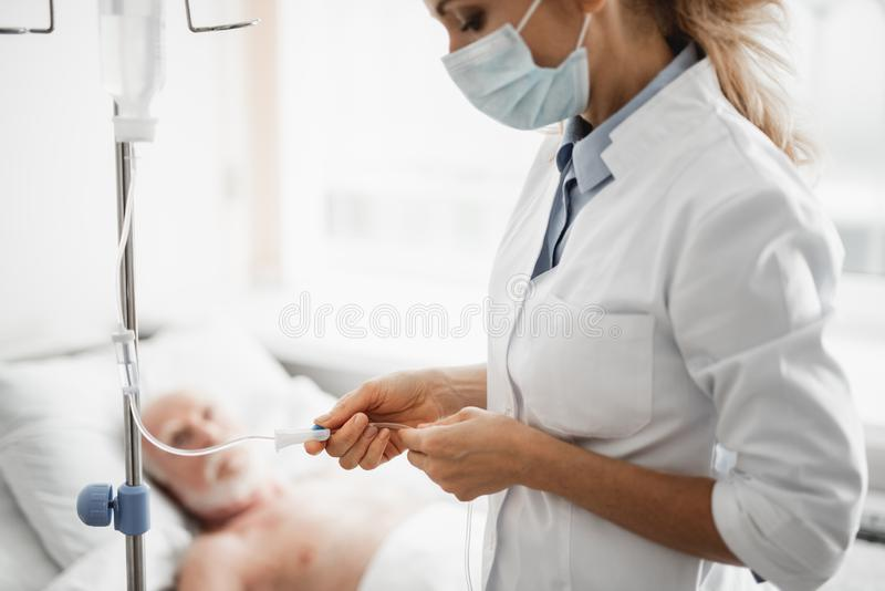 Doctor in protective mask checking intravenous drip in hospital room royalty free stock image