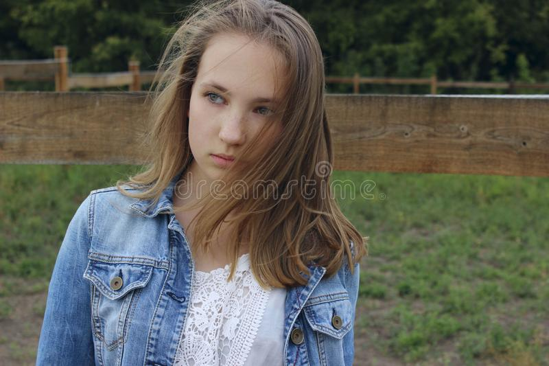 Cropped portrait of a girl in a denim jacket with developing hair. Caucasian teenage girl looking to the side outdoor, close up. stock photography