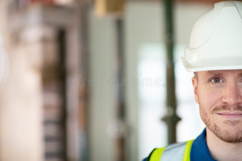 Cropped Portrait Of Male Construction Worker On Building Site Wearing Hard Hat royalty free stock image