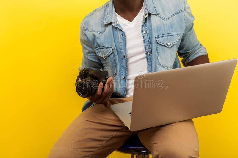 Cropped portrait of male photographer holding digital dslr camera and laptop. isolated on yellow background royalty free stock photography