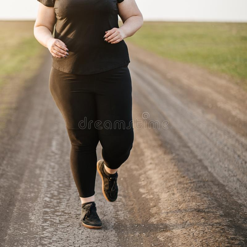 Cropped portrait of overweight runner go jogging. Outdoors. Weight losing, sports, healthy lifestyle stock photo