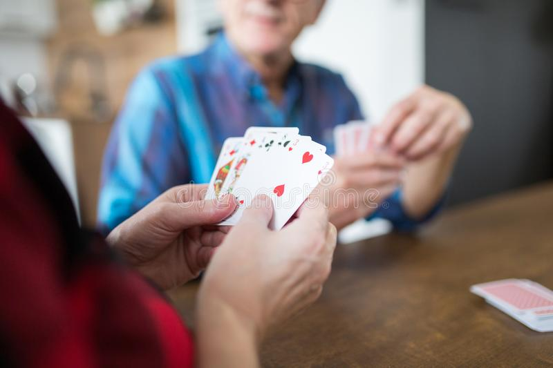 Senior lady playing cards with her husband stock photography