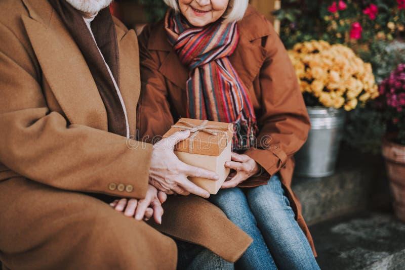Senior gentleman in coat giving present to wife stock photography