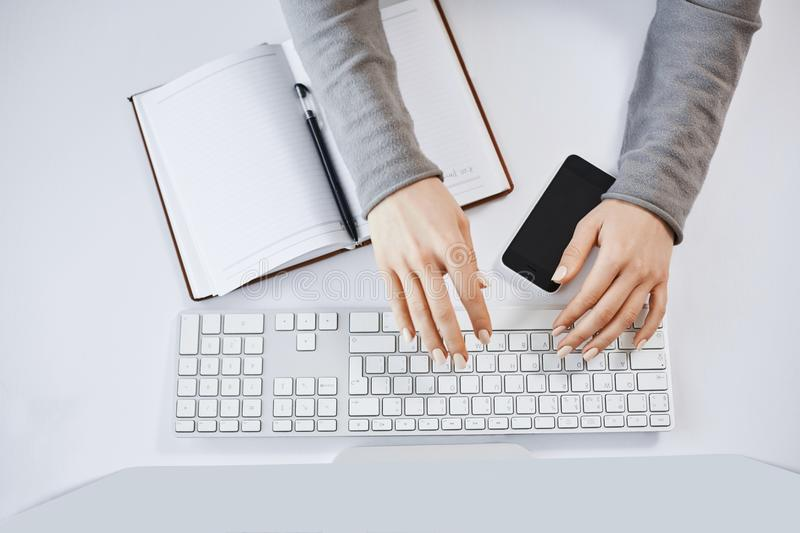 Cropped portrait of woman hands typing on keyboard and working with computer and gadgets. Modern female freelancer stock image