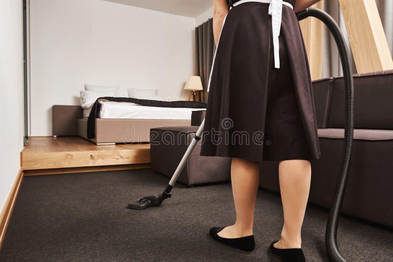 Cropped rearview żeńska housemaid cleaning podłoga żywy pokój z próżniowym cleaner w pośpiechu i, być ruchliwie zdjęcie royalty free