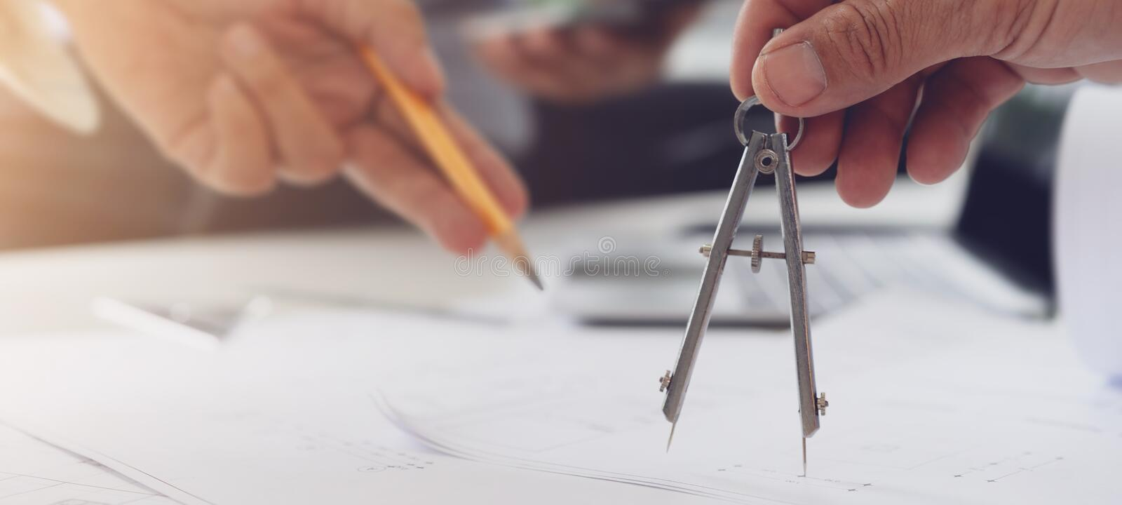 Cropped shot of architect colleagues sketching and discussing about construction plans on blueprint at construction site office royalty free stock images