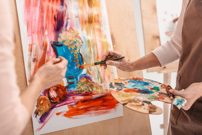 cropped shot of artists with palette painting still life on easel stock photography