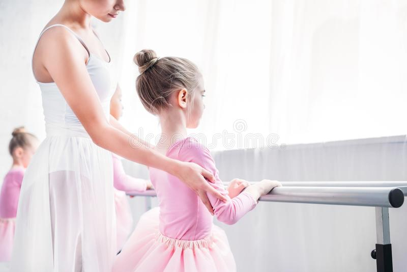 Cropped shot of ballet teacher exercising with kids. In ballet school royalty free stock photo