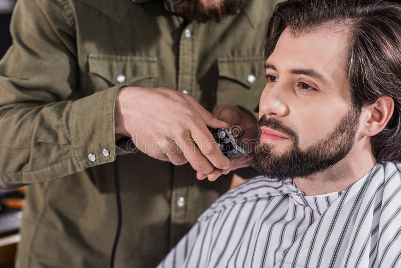 cropped shot of barber shaving client stock photo